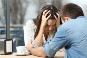 Man comforting a sad depressed girl